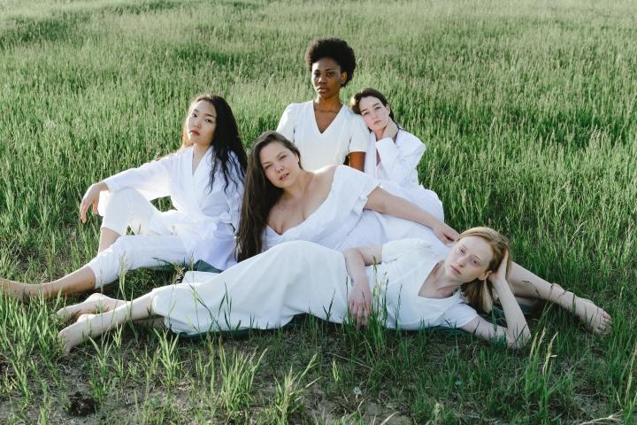 Femmes de différentes couleurs de peau et morphologies assises dans l'herbe